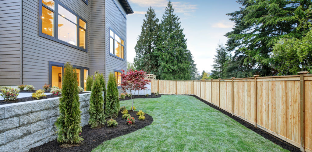 Luxurious contemporary three-story wood siding home exterior in Bellevue. Nice backyard landscape with well kept lawn flower beds and wooden fence.